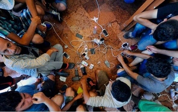refugees charging their mobile phones