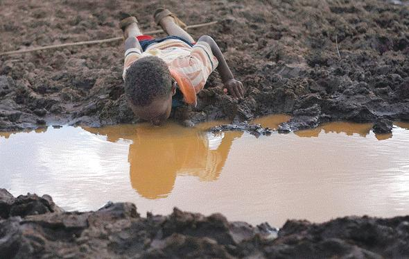 child drinking water from a mud pool